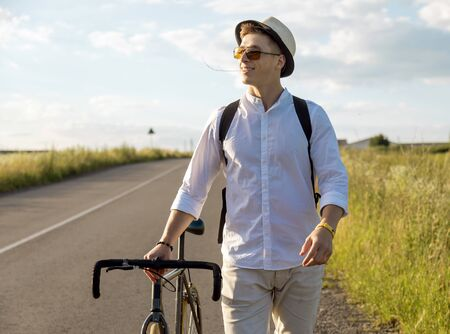 Contented cyclist guy walking by feet with a grass stalk in his mouth on a sunset background