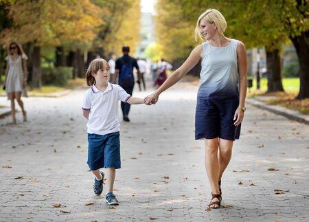 Gelukkig speciaal kind en zijn liefhebbende moeder lopen langs een parkpad in de vroege herfst
