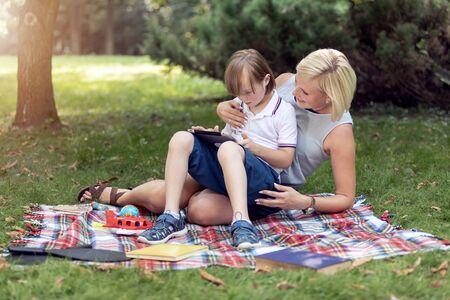Geconcentreerde jongen en zijn moeder scrollen op internet via tablet tijdens rust in het park