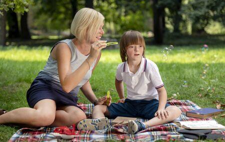 Geestelijk gehandicapte jongen kijkt met belangstelling naar de zeepbellen die door zijn moeder worden geblazen
