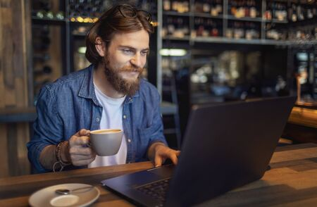 Young bearded freelancer checking email via laptop while having morning coffee in a loft bar
