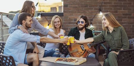 Youngsters spend spare time on a loft terrace with beer, pizza and guitar