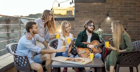 True friends having beer and pizza and listen their pal playing the guitar on a sunset loft terrace
