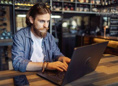 Young man with beard and moustache using laptop in a loft cafe