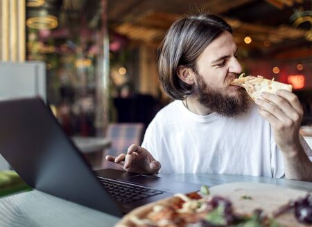 Young freelancer male snacking while working by laptop in a summer cafe