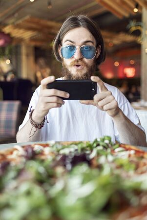 Young surprised male customer can not stop making and sharing the photo of the pizza served