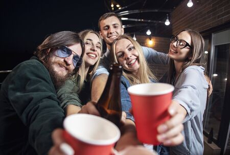 Portrait of cheerful friends having party and demonstrating their beverage to the camera close-up