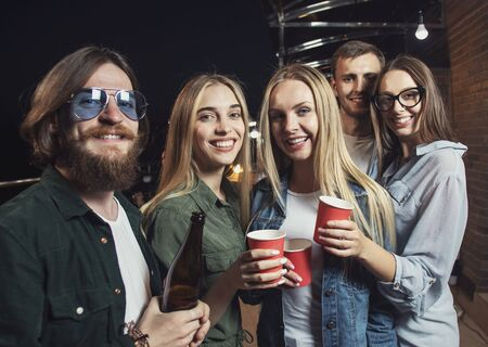 Portrait of merry friends posing with paper glasses during party on a night balcony