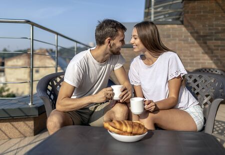Young couple has a sweet talk during an outdoor breakfast on a terrace