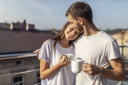 Sweet young couple has their morning coffee on a sunny balcony