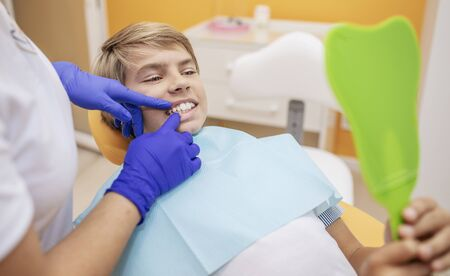 Contented teenage patient looking at his cured teeth in mirror