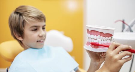 Teenage boy showing the dentist the way he usually brushes his teeth
