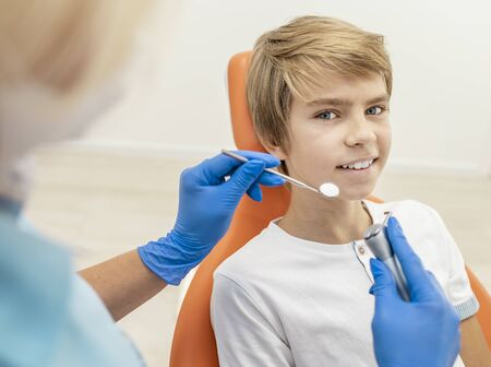 Inspired blond boy is ready for his teeth to be examined by dentist Archivio Fotografico