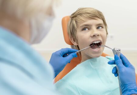 Boy with water spray syringe and dentist probe in his mouth looking at the dentist