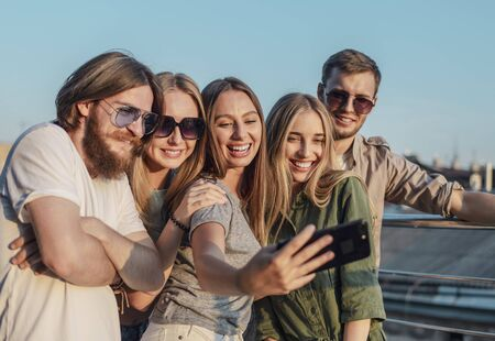 Group of friends make selfie on the edge of a balcony lit by sunset sun Archivio Fotografico - 145147732