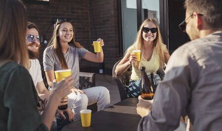 Cute girl raises her glass during a Friday friends party on a sunset terrace