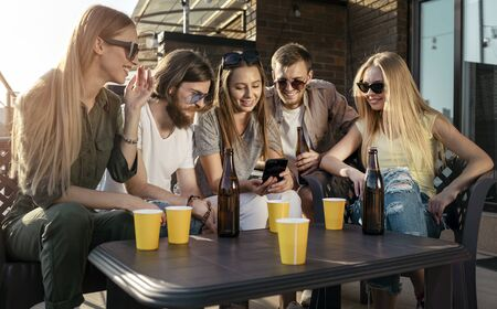 Cheerful youngsters posting photos of their party in social media Stockfoto