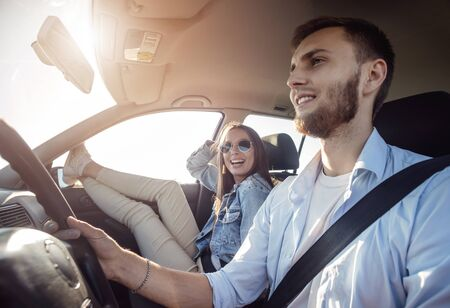 Smiling beautiful brunette girl relaxing with her legs stretched into the window while her boyfriend driving a car