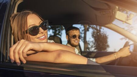 Cute brown-haired girl relaxing in rays of sunset sun while her boyfriend driving a car through countryside Archivio Fotografico - 145147750