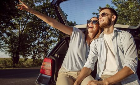 Young cheerful couple admires the countryside views while sitting in the car trunk in the rays of sunset sun