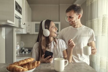 Beloved couple enjoys the company of their own during breakfast in the kitchen