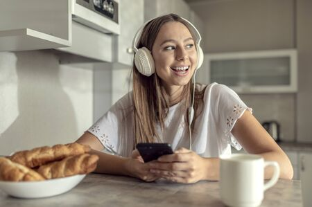 Pretty cheerful young woman enjoying her morning coffee with croissants and her favourite music