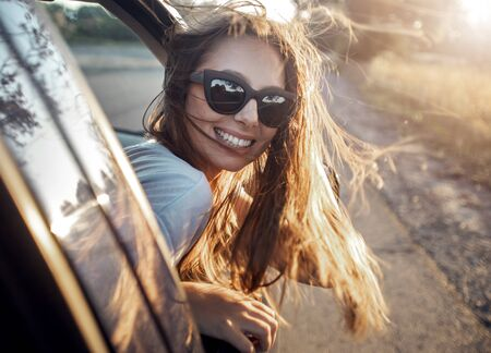 Cute brunette with long fluttering hair leaning out of the window of a car