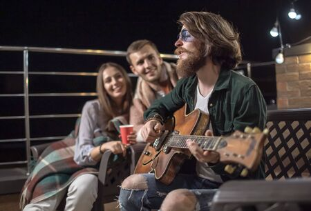 Young couple listening to their friends romantic guitar-accompanied song on a cozy balcony after sunset