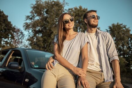 Beautiful travelling couple resting on car hood lit by sunset rays