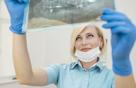 Enthusiastic young female dentist looking at the teeth and jaws radiography film Archivio Fotografico - 145147775