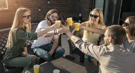 Group of friends touch glasses as they have their Friday beer party