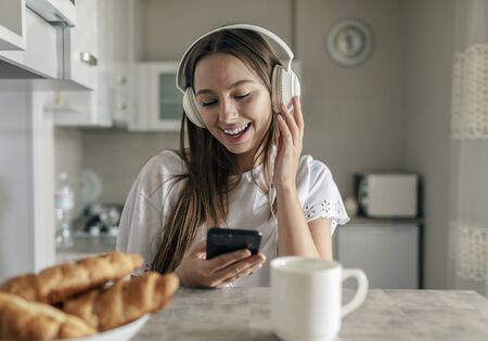 Cute young girl listening to her favourite music while having breakfast