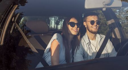 Portrait of young girl and her boyfriend posing in car lit by sunset sun 版權商用圖片