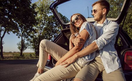 Young cheerful couple hugging while sitting in the car trunk in the rays of sunset sun