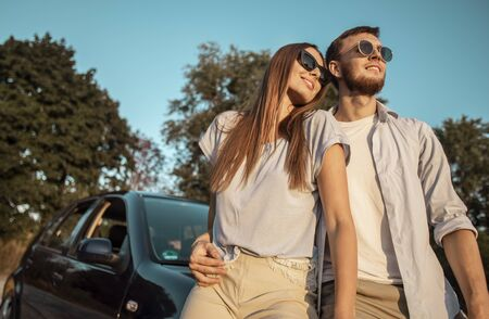 Loving couple posing on a sunset countryside road leaning against car hood low angle view Stockfoto