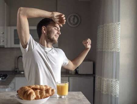 Young man stretches himself in a sunny kitchen with tasty croissants and orange juice waiting for him