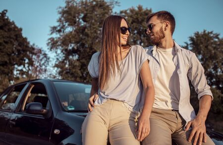 Young man and woman talking while sitting on a car hood on a countryside road