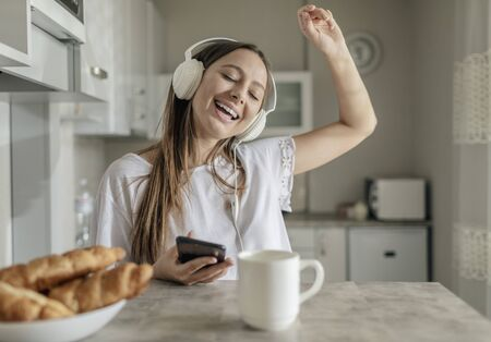 Young lady can not stop dancing while listening to the music alongside with breakfast