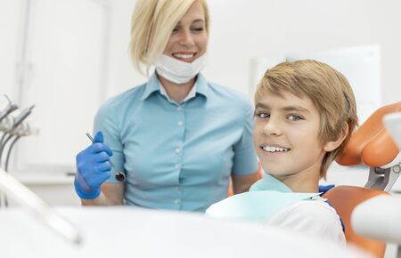Young smiling boy looking at the camera while sitting in a dental chair Stockfoto