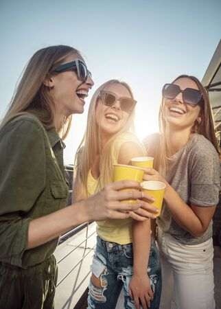 Smiling pretty women in sunglasses drinking on a sunny balcony