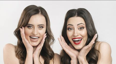 Portrait of smiling dark-haired girlfriends with naked shoulders showing surprise emotions isolated white background Archivio Fotografico