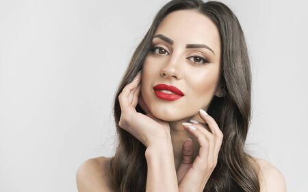 Portrait of glamour brunette with red lips touching her tender face skin isolated white background copyspace