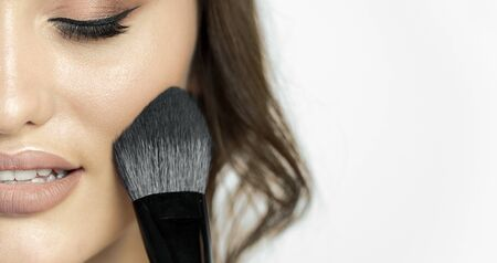 Cropped closeup photo of young cute woman using makeup brush isolated white background copyspace
