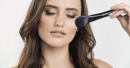 Brown-haired young beauty gently using a makeup brush isolated white background