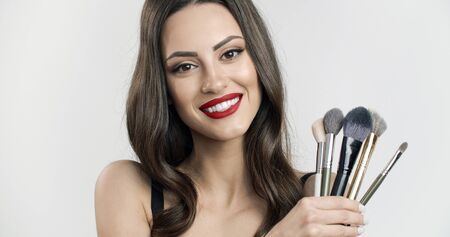 Chic brown-haired model girl with naked shoulders demonstrating a bunch of makeup brushes isolated white background