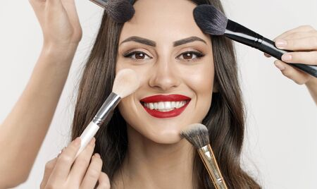 Conceptual portrait of multiple makeup brushes touching young womans face skin isolated white background Archivio Fotografico