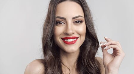Portrait of young smiling cute woman with red lips, wavy brown hair and fingers making a circle isolated white background