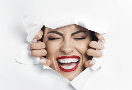 Pretty screaming woman with her eyes closed is struggling to break through a white material wall