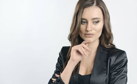 Brown-haired young business lady in black garments thinking with her hand under her chin isolated white background Archivio Fotografico