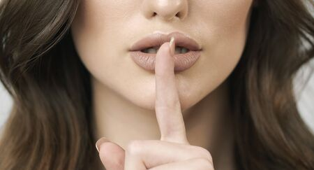 Cropped closeup of brown hair woman shushing with her index finger on her lips